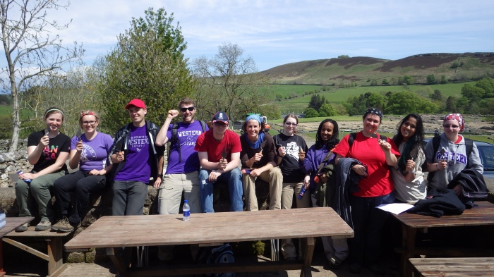 The team sitting on the shed wall with their new trowels. Dan is particularly happy.