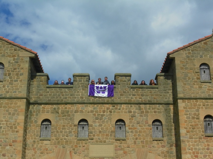 The crew displays the Western flag at the top of reconstructed Roman fort gate at South Shields (Roman 'Arbeia')