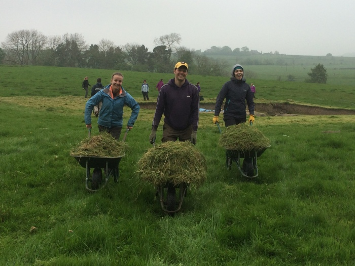 Today's Archaeology--it's all important! Monika, Alex and Veronica push (very light) wheelbarrows full of grass.